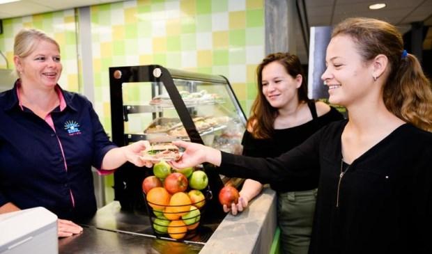 Claudia de Bleije (links) overhandigt een gezond broodje aan een leerling.