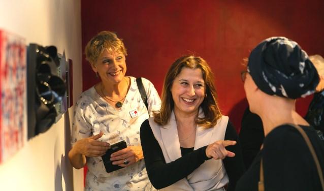 Wethouder Koser Kaya (midden) in gesprek met kunstenaars van De Ploegh tijdens de opening van '25x25x25'.