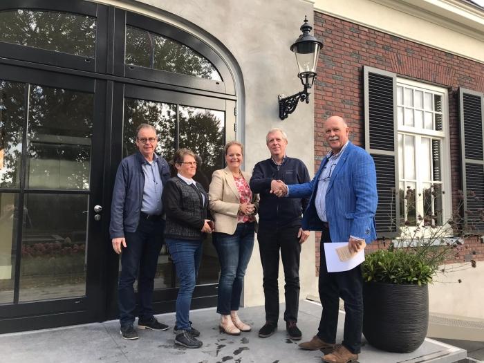 Henk van den Oever van de Stichting Idee in Uitvoering feliciteert Jan Schut van de Stichting Vakantieweek Ede.
