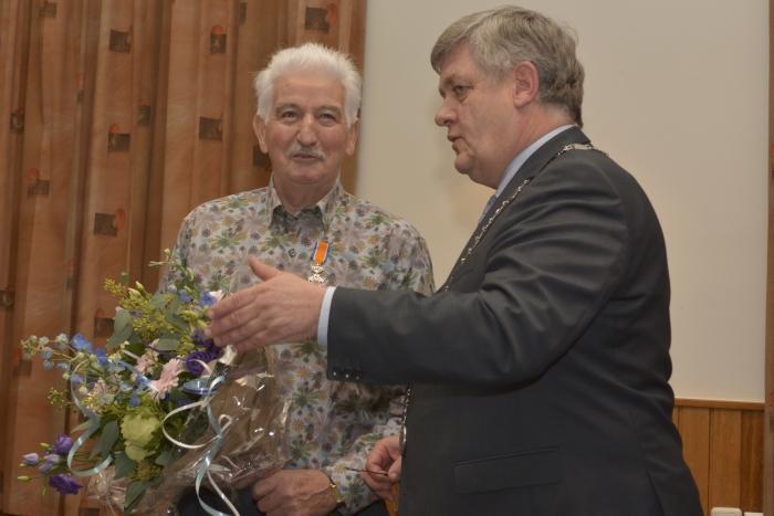 Harmen Teunissen krijgt zijn Koninklijke onderscheiding uitgereikt door burgemeester Lambooij