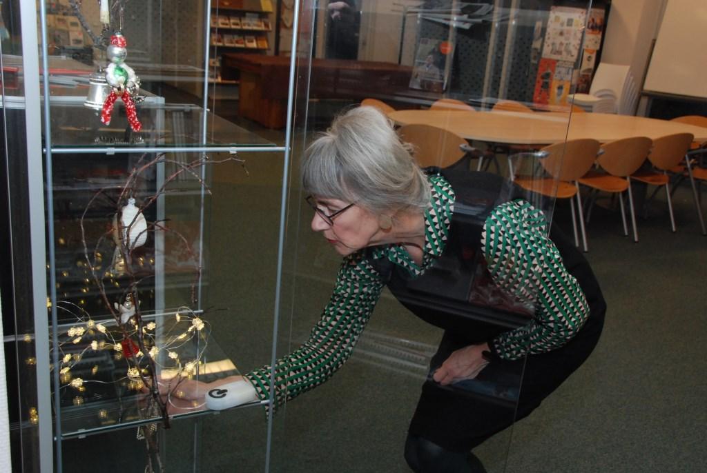 Ingrid Nagtegaal richt de vitrines in de bibliotheek in met antieke kerstversiering. Adriaan Hosang © BDU media