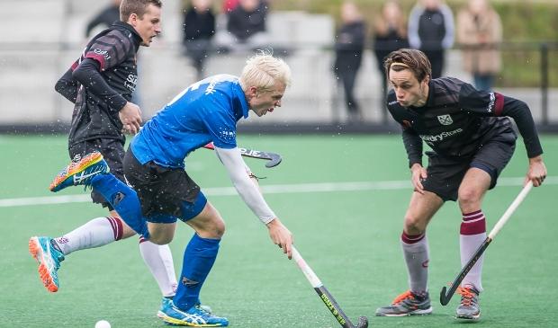 <p>Luke Dommershuijzen (in het blauwe MHC Ede shirt) maakt een mooie periode door. Maar mist competitiehockey met Amsterdam ook.</p>