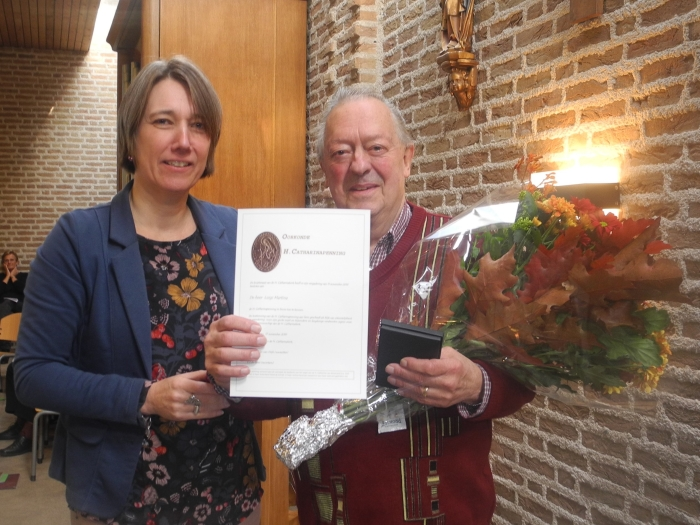 Mevr. Slaghekke-van Wijk overhandigt Catharinapenning en oorkonde aan de heer Martina.