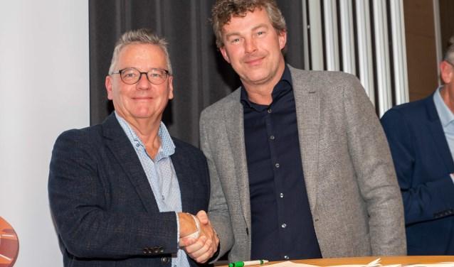 Roelf Polman (r), directievoorzitter Rabobank Merwestroom, en Cees Boer drukken de hand voor nog eens drie jaar samenwerking.