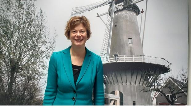 Wethouder Erika Spil bij een poster van de molen van Werkhoven op het gemeentehuis