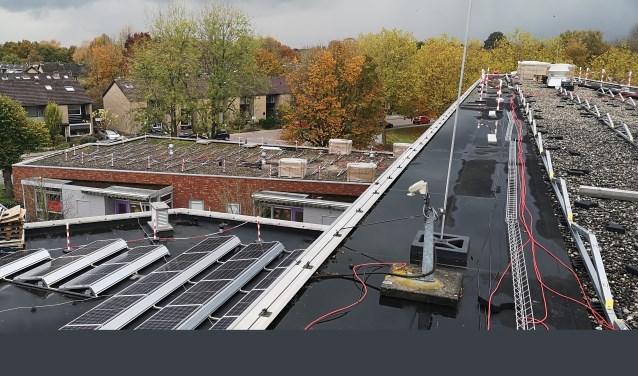 De installatie van de zevenhonderddrie zonnepanelen op de daken van De Binder vordert vlot.