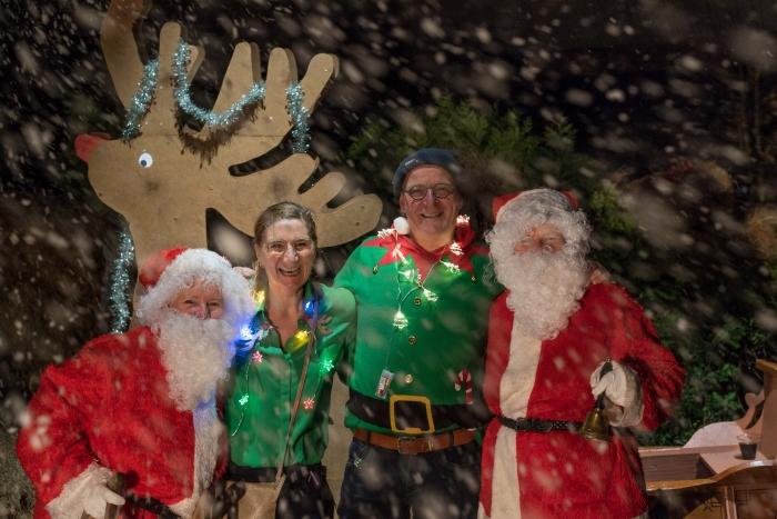 Feestgangers werden opgewacht door een fotograaf, twee kerstmannen en een wel heel plaatselijke sneeuwbui.
