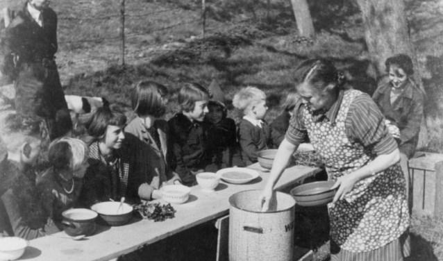 Mevrouw Marsman deelt eten uit aan kinderen op de Rijndijk in Wijk bij Duurstede