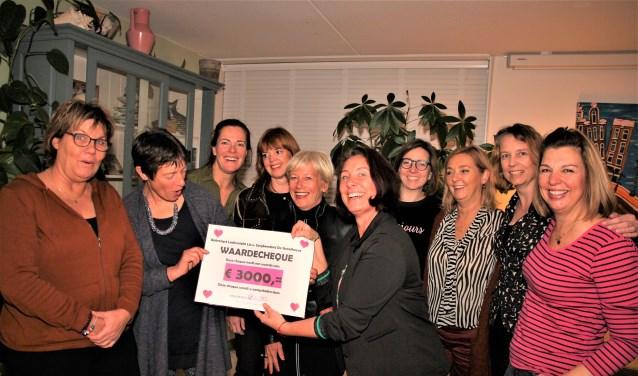 Carola van Staaveren (2e van links) krijgt de cheque aangeboden.
