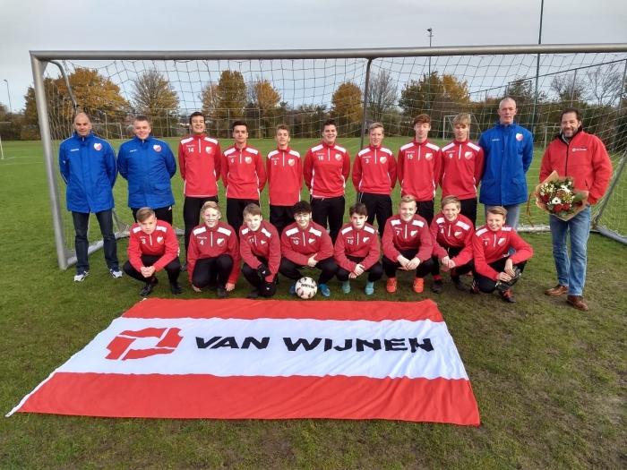 Spelers en trainers van de JO17-2 poseren samen met dhr. van MImpen namens sponsor Van Wijnen in hun nieuwe trainingspakken