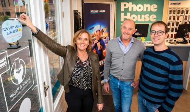 Wethouder Didi Dorrestijn-Taal hangt samen met Anton Kooijman van The Phone House en Jan-Peter Pols van het Energieloket Barneveld de eerste poster op.