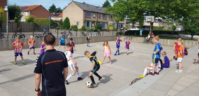Buurtsportcoach Patrick van de Ven met sportende kinderen tijdens de vakantie