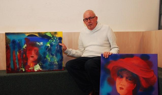 Hans van Leeuwen met twee van zijn schilderijen.