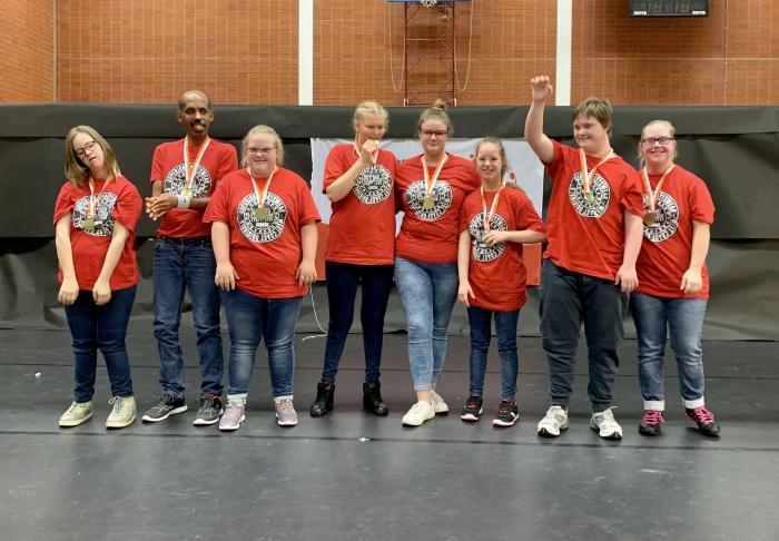 De trotse groep dansers met hun gewonnen medaille
