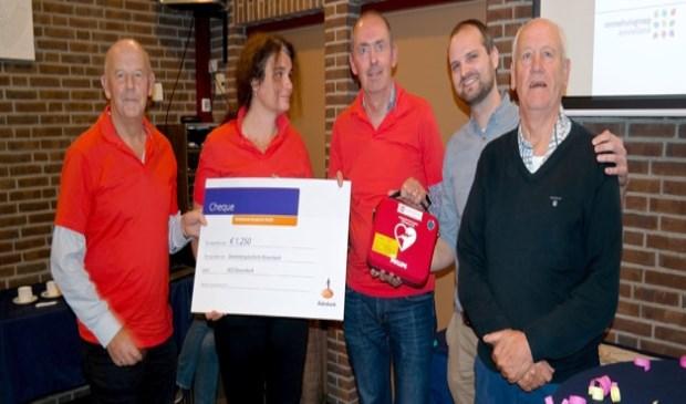 Enkele leden van de projectgroep nemen de AED én een cheque van 1.250 euro in ontvangst van Rabobank Amstel en Vecht. Van links naar recht: Gerard Miltenburg, Lisanne de Boer, Edwin Barentsen, Arie van Noord en Jorick Houtkamp.