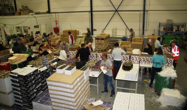 Medewerkers van het productiebedrijf pakken kerstpakketten in.