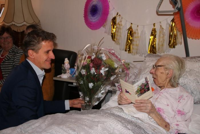 Mevrouw Meerkerk ontvangt bloemen van de bestuurder van De Lange Wei omdat zij 100 jaar is geworden