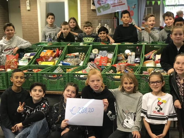 Leerlingen van OBS Twickel met de gevulde kratten en het opgehaalde bedrag voor de voedselbank