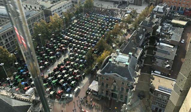 tractoren op een rij aan de markt en huizen van bovenaf bekeken