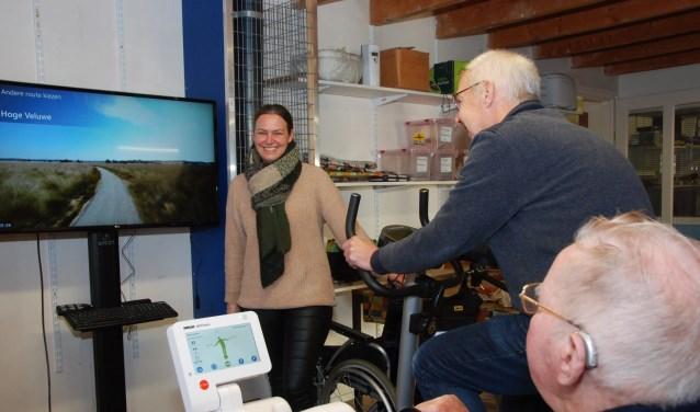 Annemien van Ginkel kijkt toe terwijl twee anderen een fietstocht over de Veluwe maken.