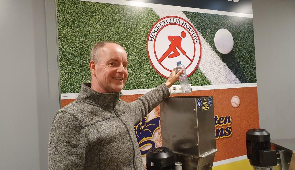 Mike staat op het punt een petflesje in de plastic shredder te laten vallen.