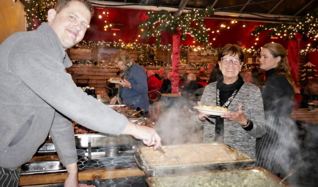 Poffertjes, oliebollen, warme chocola, aan alles is gedacht op de Warme Witte Winterweken. Alie van Nieburg (midden) doet al dertig jaar mee.