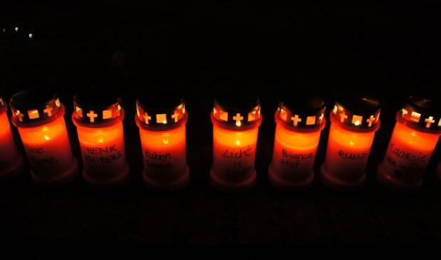 Op de kaarsen staan verschillende teksten, waaronder één met 'Licht is leven'.