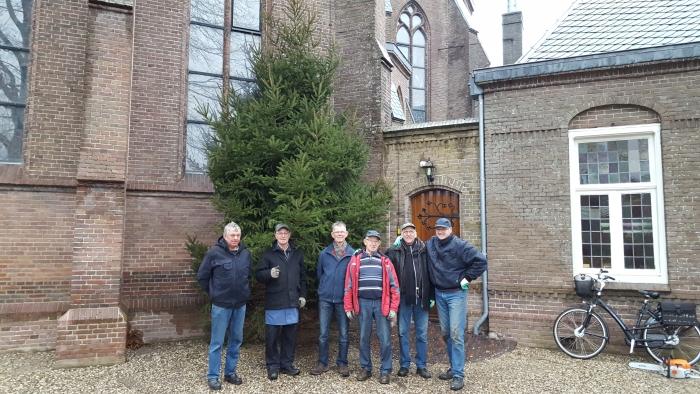 vrijwilligers zetten de kerstboom op zijn plek