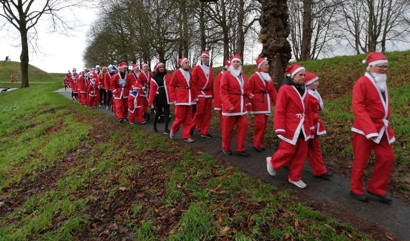 In grote getale lopen of rennen de kerstmannen over de stadswallen.