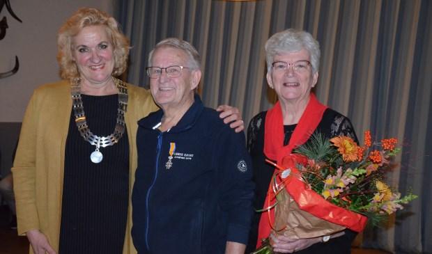 De onderscheiding voor Harry van Impelen, de bloemen voor zijn vrouw Wil