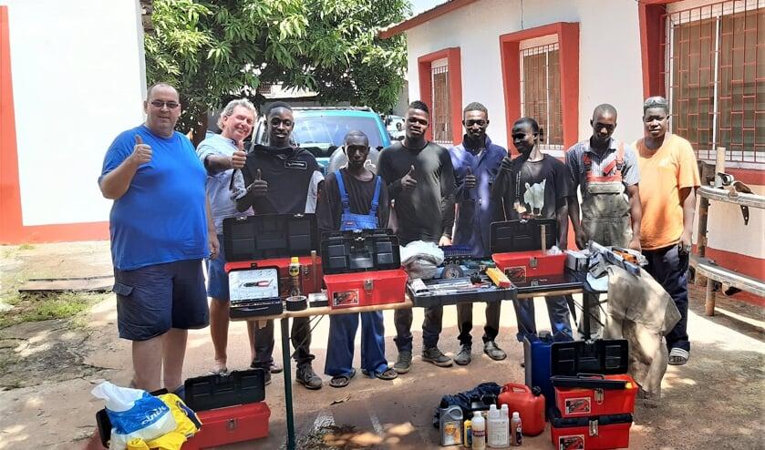 Marco legde de blijdschap bij de toekomstige automonteurs vast. Links de Duitse initiatiefnemer van de school, naast hem Ysbrand.