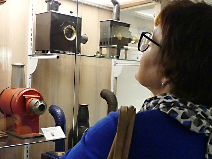 Een bezoeker bewondert een aantal toverlantaarns, die tentoongesteld zijn in het Kijk en Luistermuseum