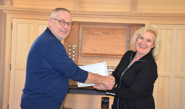 Wethouder Wil Kosterman overhandigt bij het orgel de cheque aan Sjoerd Vredenberg