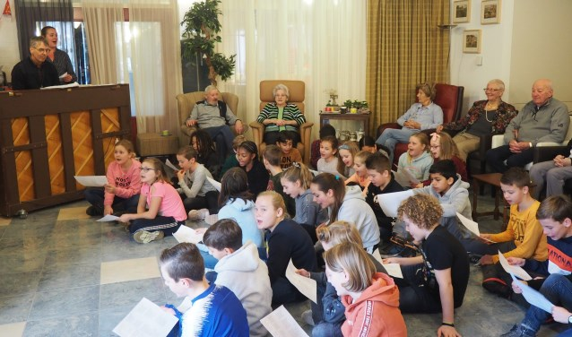 Kinderen van de Uilenburcht zingen, onder pianobegeleiding van Meester Dik, sinterklaasliedjes met de bewoners van Rehoboth.