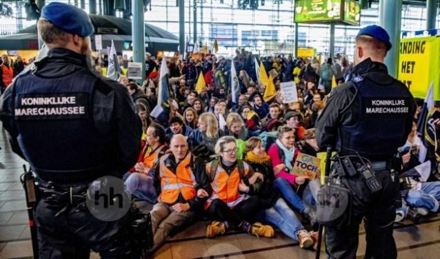 Een grote groep actievoerders zit nog gearmd in de hal omringd door marechaussees.