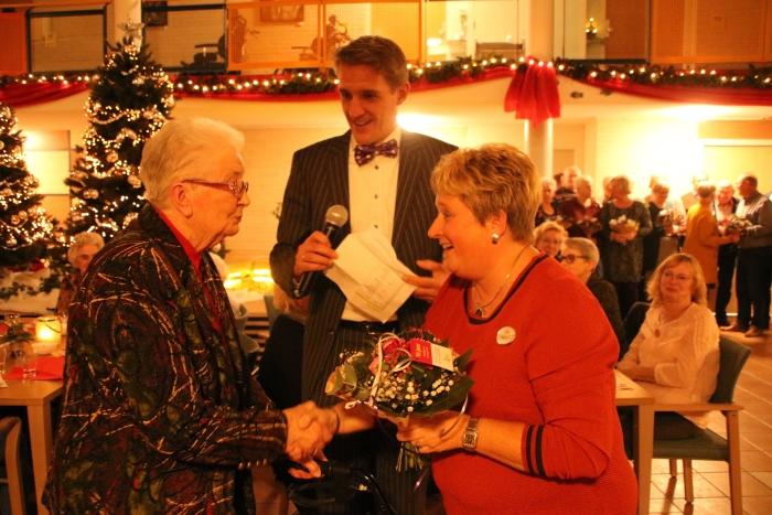 Eén van de jubilerende vrijwilligers van De Lange Wei ontvangt een bloemetje van vrijwilligerscoordinator Francis 't Hooft. Op de achtergrond: Bestuurder Sander van IJsseldijk