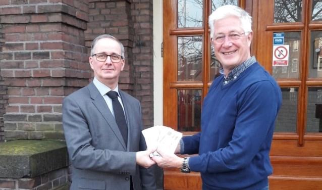 De voorzitter van Rotary Velsen, Jan Willem Bruntink, overhandigt de kaarten aan de directeur van het Vellesan College, Marc Boelsma.