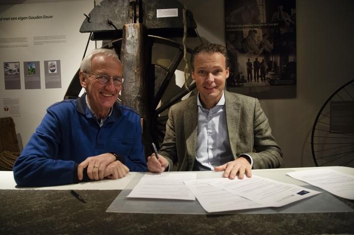 Jan Langman, directeur Touwfabriek Langman (rechts en Jan Cozijnsen, voorzitter Stichting Oud Nijkerk (links), ondertekenen het vernieuwde sponsorcontract. Op de achtergrond het grote wiel van de touwslagerij.