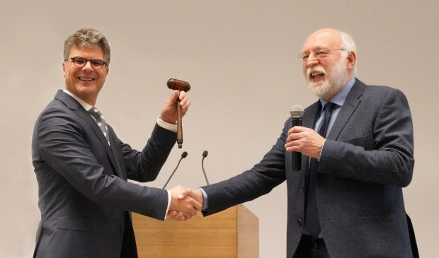 Hans Oosters (links) ontvangt de voorzittershamer uit handen van vicevoorzitter Kees de Kruijf