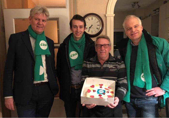 Jan Wagenaar neemt een taart in ontvangst van Bert Komdeur