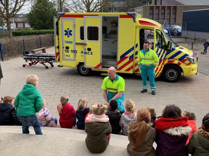 Hier wordt door een ambulancemedewerker iets verteld over de ambulance