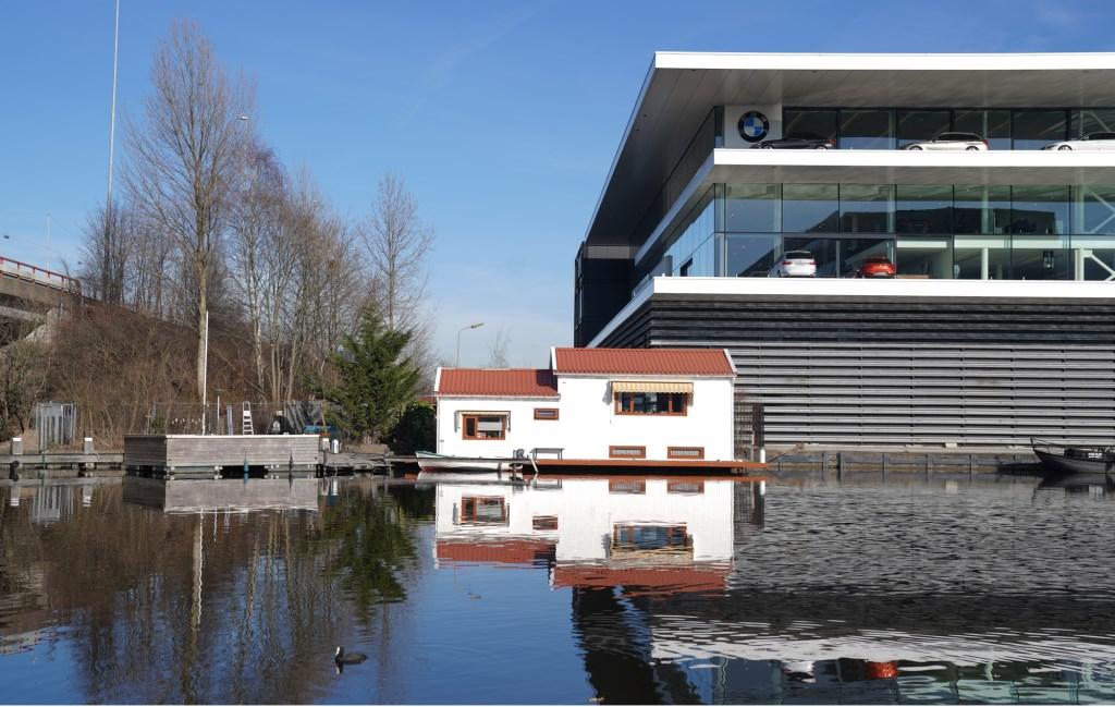 De woonboot van Jan wordt overschaduwd door de BMW garage.  Naomi Heidinga © BDU media