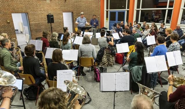 Het orkest tijdens de repetitie. Naast de dirigent (Geert Schrijvers) staat Gé Reinders.
