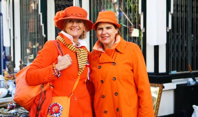 Twee in oranje geklede dames vieren Koningsdag in Baarn