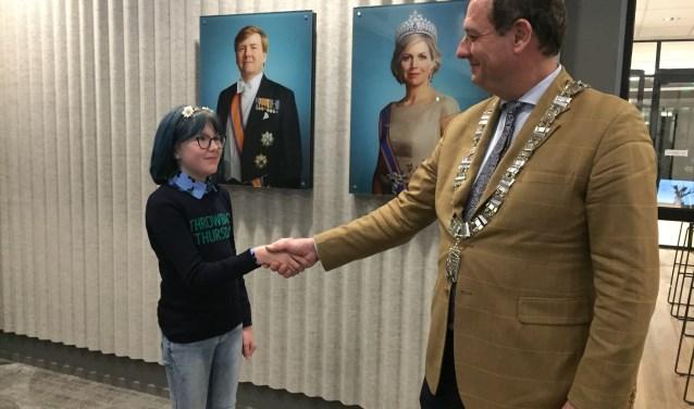 Burgemeester Gerolf Bouwmeester feliciteert zijn jeugdige ambtsgenoot Lotte van den Tweel.