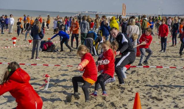 Kinderen leven zich sportief uit op het strand tijdens de Koningsspelen