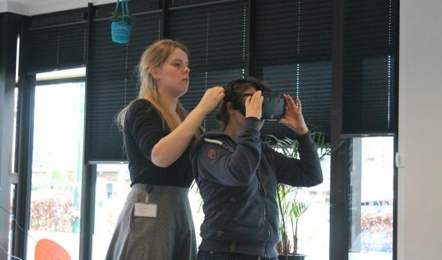 Marleen helpt Indra om de VR bril op te zetten