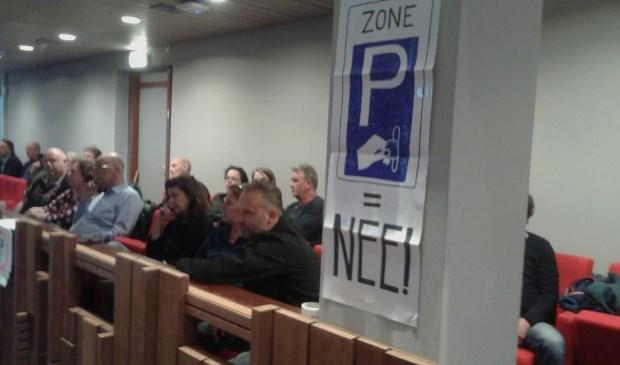 Boze burgers in de raadszaal bij een debat over betaald parkeren.