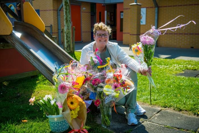 Juf Judith met haar bloemen bij peuterspeelzaal De Ark