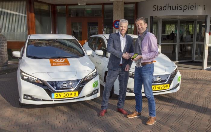 Buurauto directeur Alex van der Woerd 'overhandigt' wethouder Hans Buijtelaar de slutels voor acht nieuwe, duurzame deelauto's